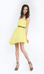 Trendy young woman in yellow dress smiling on white background
