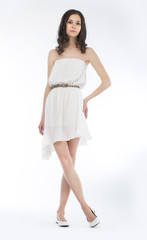 Young charming female in dress posing over white background
