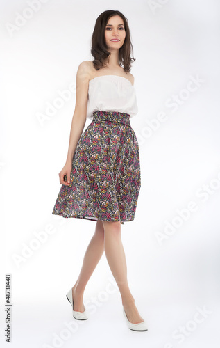 Trendy young woman in blouse and skirt posing isolated
