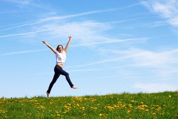 happy smiling girl jumping outdoor against blue sky