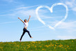 happy jumping girl with drawn heart against blue sky