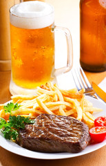 grilled steak with mug of beer