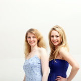 Two smiling blonde women posing on white background