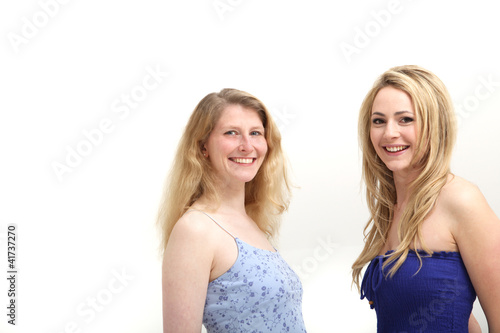 Two smiling women posing on white background