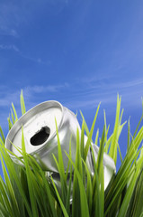 Recycle concept. Drink can on green grass