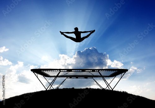 silhouette of female gymnast on trampoline in front of clouds
