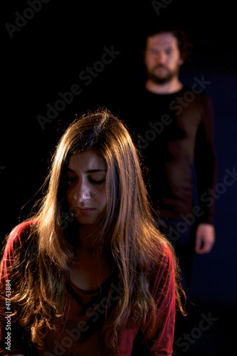 Sad woman oppressed by dark man