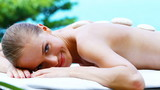 Beautiful girl relaxing on spa bed in tropical outdoor