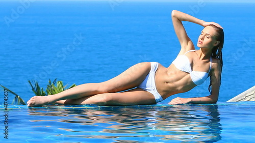 Gorgeous beauty lying at the edge of swimming pool
