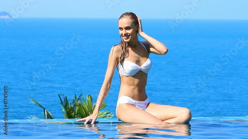 Woman sitting at the edge of infinity swimming pool