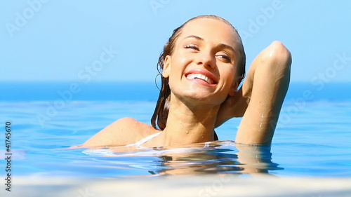 Beaufitul woman resting in infinity swimming pool