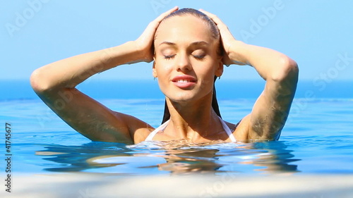 Sensual beauty relaxing in tropical swimming pool with a view