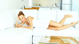 Happy woman jupms on white sofa and smiling