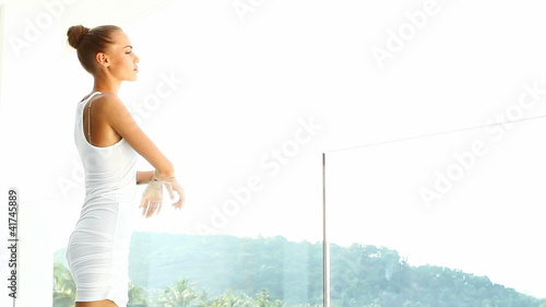 Lovely woman enjoying tropical view from her balcony