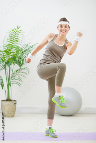 Happy fitness woman making gymnastics