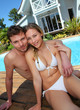 Portrait of couple sitting by swimming-pool