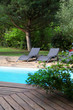 Closeup on long chairs set by private pool