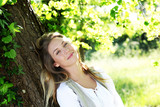 Smiling blond woman leaning on tree