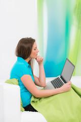 junge frau nachdenklich mit laptop auf dem sofa