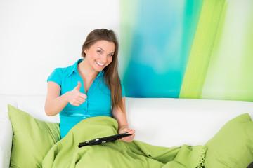 erfolgreiche junge frau mit touchpad auf dem sofa