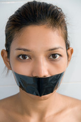 Young woman with mouth sealed..