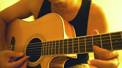 Man playing acoustic guitar with warm light