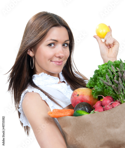 woman holding a paper shopping bag full of groceries