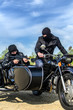 Two armed men riding a motorcycle with a sidecar