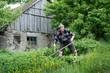 Bauer mäht vor Bauernhof