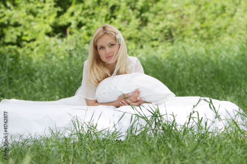 young beautiful woman relaxing on white bed on natural backgroun