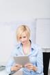junge frau arbeitet mit tablet im büro
