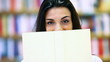 woman hides behind a book, cover is blank