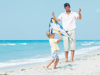 boy with father on beach playing with a kite