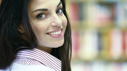 portrait of beautiful young female student in library