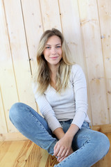 Blond woman with blue jeans sitting on the floor