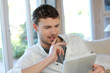 Man sitting in sofa with electronic tablet