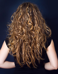 Young attractive woman with long curly hair on a dark background