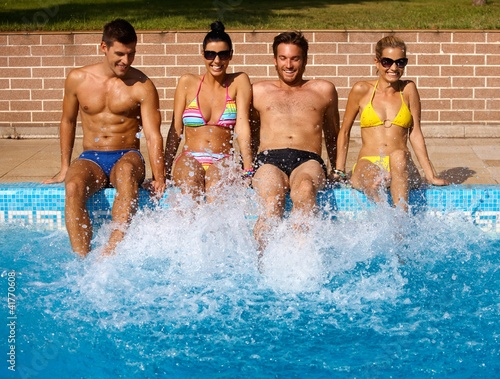Young people having summer fun by pool