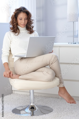 Pretty woman in modern chair with laptop