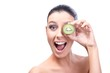 Woman holding kiwifruit front of eye laughing