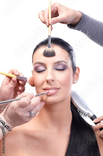 Makeup artists working on beautiful model