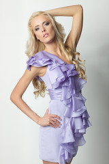 Beautiful blond female posing in lilac summer dress