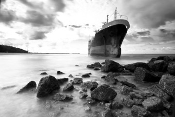 Cargo ship run aground on rocky shore shore, black and white