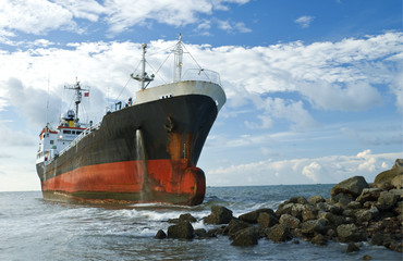 Cargo ship run aground on rocky shore shore