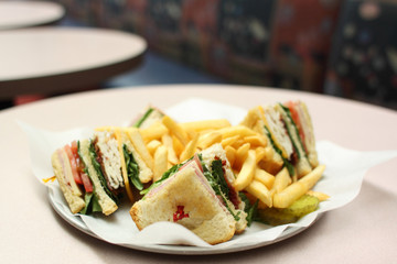 Delicious club sandwich with french fries.