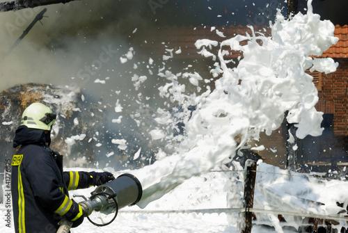 Leinwanddruck Bild Feuerwehr löscht Scheunenbrand mit Schaum