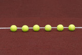 Yellow tennis balls in-line on court with synthetic surface poster