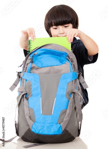 Boy taking notebooks out of backpack