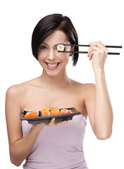 Smiling young female holding sushi with a chopsticks