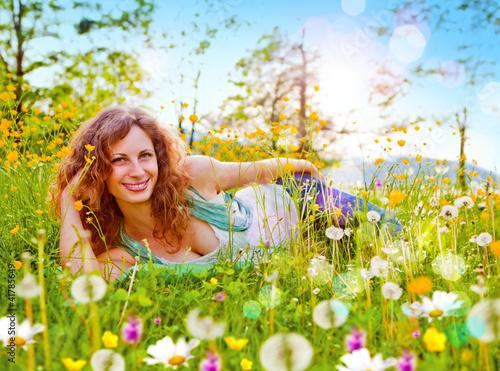 Mädchen liegt entspannt in einer Blumenwiese / dandelion-8